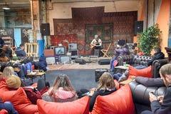 Les personnes non identifiées détendent et écoutent la musique sur le marché local i Image libre de droits