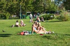 Les personnes non identifiées les prennent un bain de soleil sur une pelouse verte de la MU reconstruite Image stock