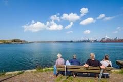 Les personnes retraitées regardent à travers l'eau sur la côte de la Mer du Nord à m image stock