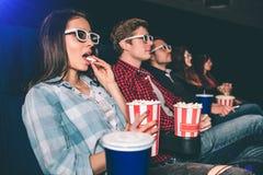 Les personnes sérieuses et concentrées observent le film Ils se reposent dans une rangée La fille de brune a un panier de popcron Images libres de droits