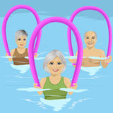 Les personnes supérieures dans la forme physique classent faire l'aérobic d'aqua avec des rouleaux de mousse dans la piscine au c Photographie stock libre de droits