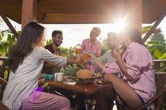 Les personnes sur la terrasse d'été prenant le petit déjeuner grillant ensemble le jus, la femme et l'homme mangent parler dans l Images stock