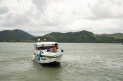 Les personnes thaïlandaises conduisent le bateau de vitesse par le pilier de Rong de coup au moori de Phuket Photos libres de droits