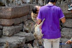 Les personnes thaïlandaises donnent la nourriture aux singes chez Phra esquintent Samyod Image stock