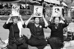 Les personnes tiennent le portrait du Roi Bhumibol Adulyadej chez Sanam Luang devant Royal Palace pour payer le respect le roi images stock