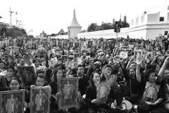 Les personnes tiennent le portrait du Roi Bhumibol Adulyadej chez Sanam Luang devant Royal Palace pour payer le respect le roi photographie stock