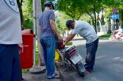Les personnes vietnamiennes remplissent réservoir de gaz dans la moto Image stock