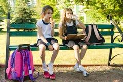 Les petites écolières attirantes d'amies avec des sacs à dos, filles se reposent sur le banc en parc après école, mangent la crèm Image stock
