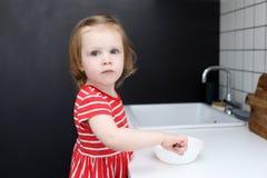 Les petites 2 années mignonnes de fille aide à faire cuire à la maison la cuisine Photographie stock