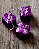 Les petites boîtes de cadeaux attachent avec des cordes sur le support en bois photo stock