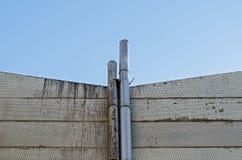 les petites cheminées (cheminée) sifflent sur le mur jaune avec le ciel bleu Images libres de droits