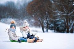 Les petites filles adorables apprécient un tour de traîneau Enfant Images stock