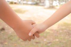 Les petites filles asiatiques tenant des couples de mains montrent ensemble Relationsh Photographie stock libre de droits