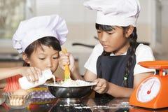 Les petites filles asiatiques versent le lait dans la farine et l'oeuf de blé Photo libre de droits