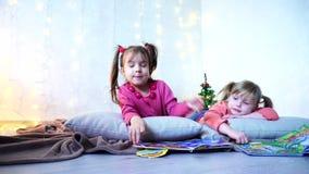 Les petites filles avec du charme jouent ensemble et causent, se trouvant sur le plancher et sur des oreillers contre le mur avec banque de vidéos