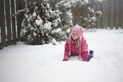 Les petites filles blondes caucasiennes joue avec la neige sur le fond de tache floue de sapin Photo libre de droits