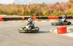 Les petites filles conduisent la voiture de kart dans un tra de emballage de terrain de jeu photographie stock