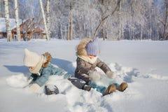 Les petites filles de sourire s'asseyent dans la neige et sourient Photographie stock