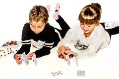 Les petites filles heureuses font la maison des cartes d'isolement sur le blanc Photographie stock libre de droits