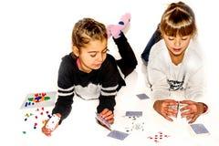Les petites filles heureuses font la maison des cartes sur le blanc Images libres de droits