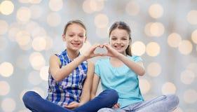 Les petites filles heureuses montrant la main de forme de coeur signent Photographie stock libre de droits