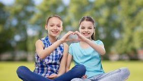 Les petites filles heureuses montrant la main de forme de coeur signent Images stock