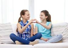 Les petites filles heureuses montrant la main de forme de coeur signent Photographie stock