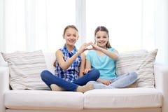 Les petites filles heureuses montrant la main de forme de coeur signent Image libre de droits