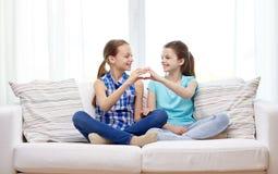 Les petites filles heureuses montrant la main de forme de coeur signent Photo libre de droits