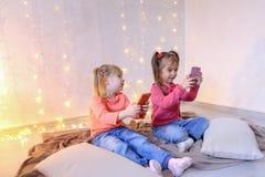 Les petites filles heureuses utilisent des smartphones pour le divertissement et s'asseyent dessus Photo stock
