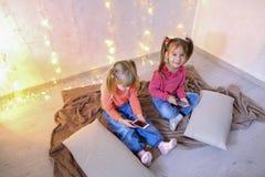 Les petites filles heureuses utilisent des smartphones pour le divertissement et s'asseyent dessus Image libre de droits
