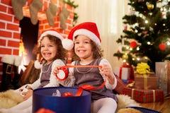 Les petites filles jumelle à Noël se reposant sur le plancher dans Santa ha Photo libre de droits