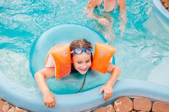 Les petites filles nage dans la piscine par un jour d'été photos stock