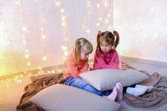 Les petites filles ont impliqué en service du comprimé et s'asseyent sur le plancher dans le brigh Photos libres de droits