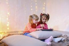 Les petites filles ont impliqué en service du comprimé et s'asseyent sur le plancher dans le brigh Image stock