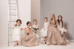 Les petites jolies filles avec des fleurs se sont habillées dans des robes de mariage Image libre de droits