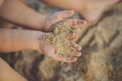 Les petites mains d'enfant tenant le portrait mou étroit de foyer de sable des vacances d'enfance d'heure d'été de côté de mer de Images stock