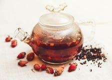 Les petites roses rouges sèches avec le thé noir dans la théière en verre Photos libres de droits