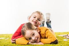les petites soeurs heureuses ont isolé le mensonge sur le tapis vert et regarder l'appareil-photo d'isolement Photographie stock libre de droits