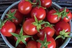 Les petites tomates-cerises rouges dans un fer bucket dans un style rustique, foyer sélectif Plan rapproché photo stock