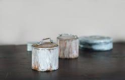 Les petites vieilles boîtes ont peint le blanc sur la table en bois Photos libres de droits