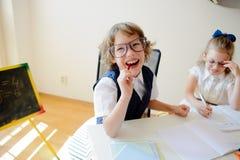 Les petits écoliers drôles en verres, garçon et fille, s'asseyent à un bureau image libre de droits