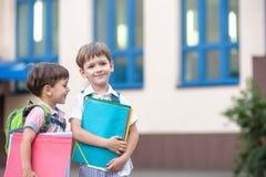 Les petits étudiants mignons d'école parlent vivement sur la cour de récréation Chil Photographie stock