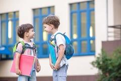 Les petits étudiants mignons d'école parlent vivement sur la cour de récréation Chil Photographie stock libre de droits