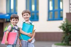 Les petits étudiants mignons d'école parlent vivement sur la cour de récréation Chil Photos stock