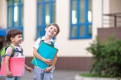 Les petits étudiants mignons d'école parlent vivement sur la cour de récréation Chil Images stock