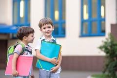Les petits étudiants mignons d'école parlent vivement sur la cour de récréation Les enfants ont une bonne humeur Matin chaud de r Photographie stock libre de droits