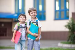 Les petits étudiants mignons d'école parlent vivement sur la cour de récréation Les enfants ont une bonne humeur Matin chaud de r Photo libre de droits