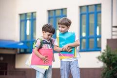 Les petits étudiants mignons d'école parlent vivement sur la cour de récréation Les enfants ont une bonne humeur Matin chaud de r Image stock