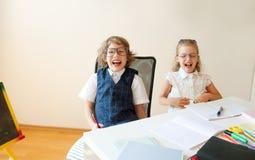 Les petits étudiants ridicules à lunettes, le garçon et la fille, partagent le même bureau images libres de droits